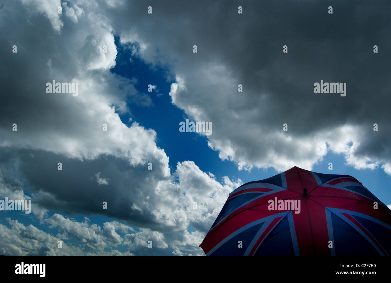 Brexit,Union jack umbrella against a cloudy, stormy sky. British economic / weather concept. - Stock Image