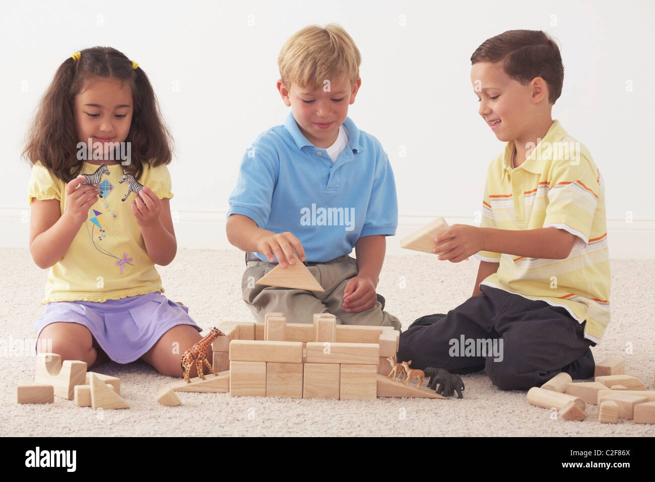 Three Children Building Noah's Ark With Wooden Blocks - Stock Image