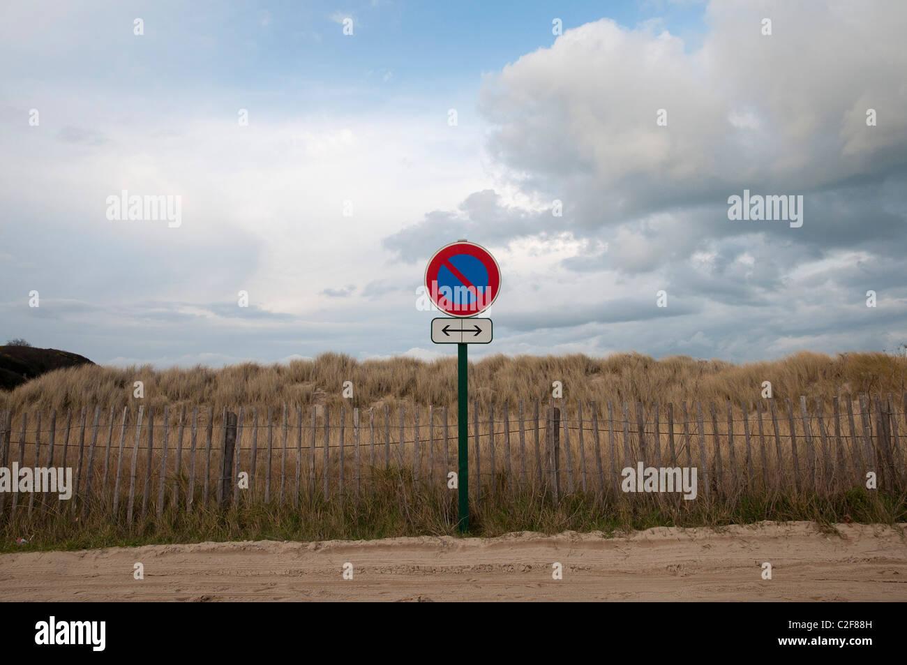 un panneau interdiction de stationner devant dunes de sable a no parking sign in front of sand dunes - Stock Image