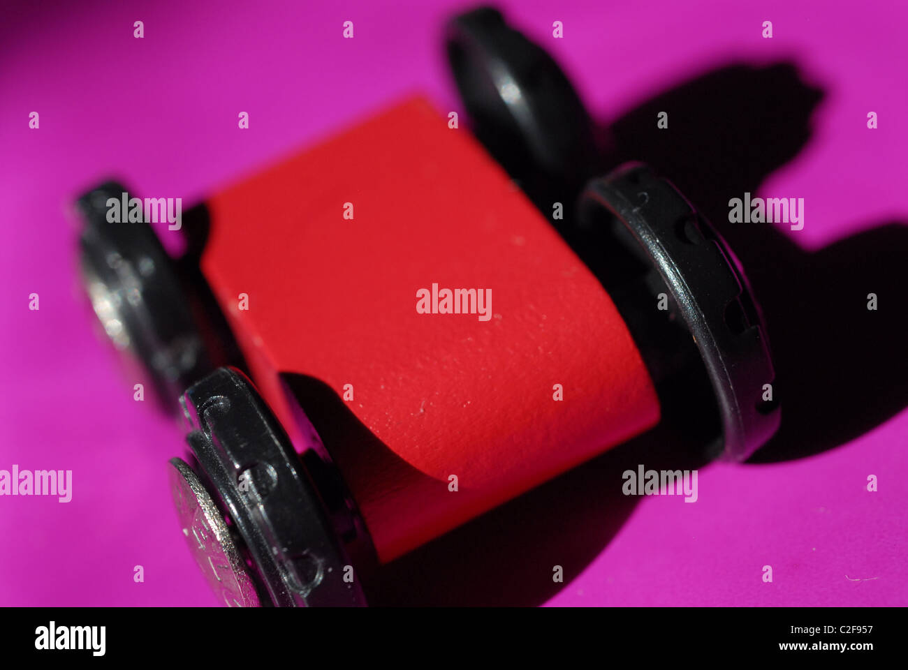 Red wooden toy car against bright pink background. - Stock Image