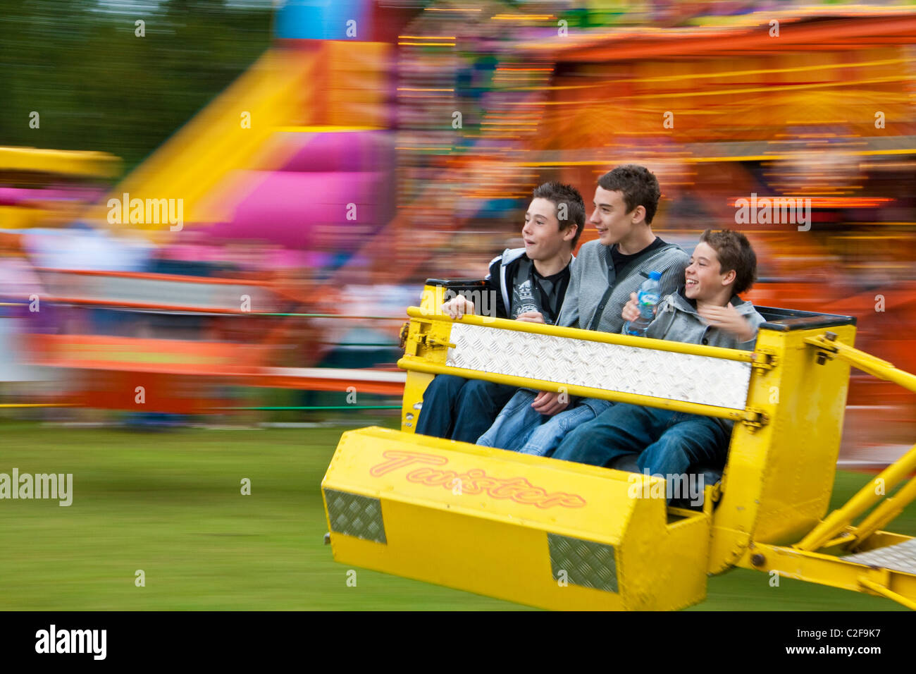 Three young boys enjoy spinning on a fairground ride - Stock Image