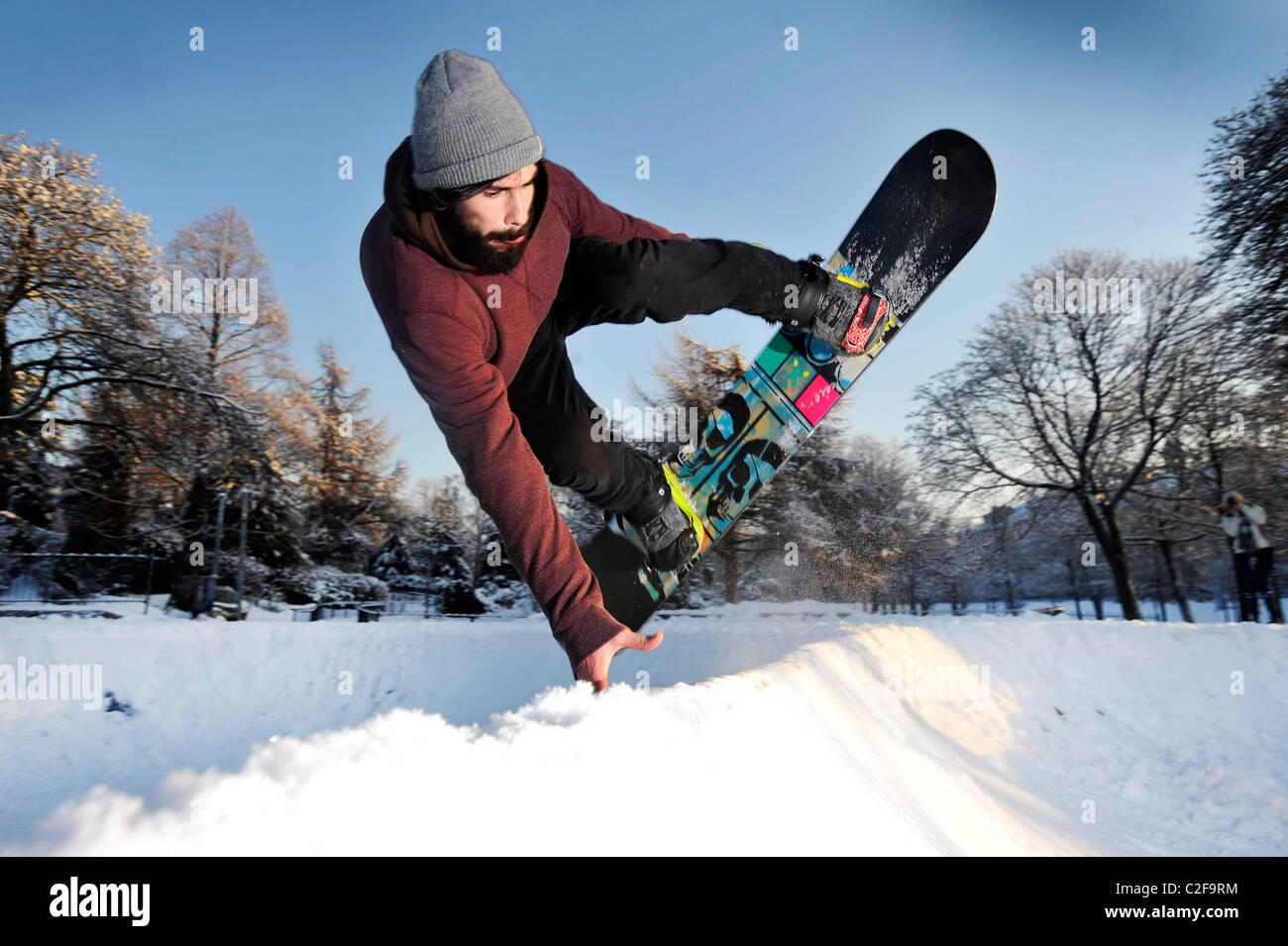 A man rides a snowboard on a snow covered skatepark in Kelvingrove Park, Glasgow, Scotland. - Stock Image