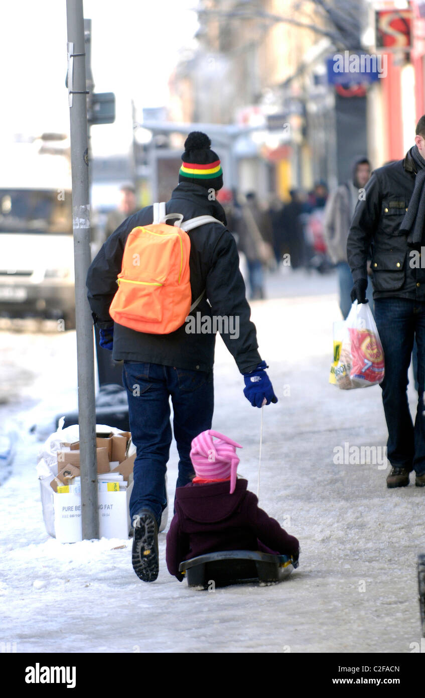 A man drags his child through the streets of Glasgow, Scotland during the coldest winter in decades. - Stock Image