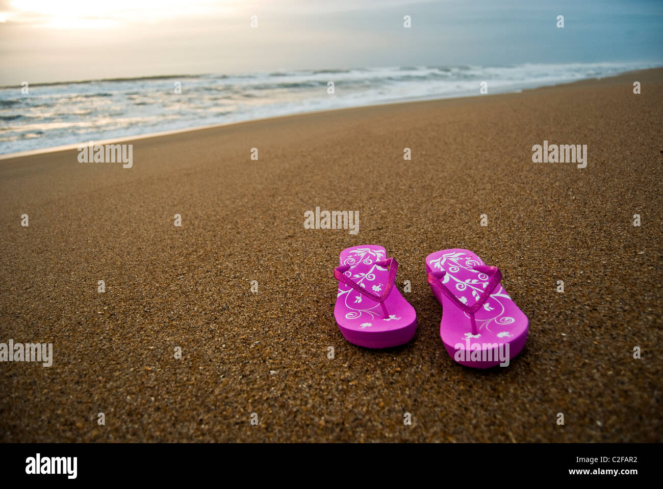 Pink women's flip-flops on an empty and clean beach at sunrise. - Stock Image
