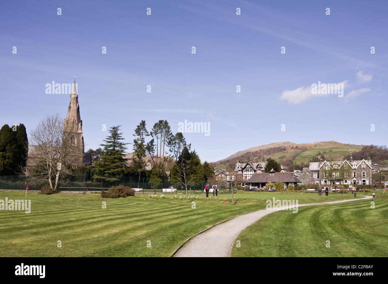 Ambleside, Cumbria, England, UK. View of Cumbrian town and St Mary's parish church from across the park putting - Stock Image