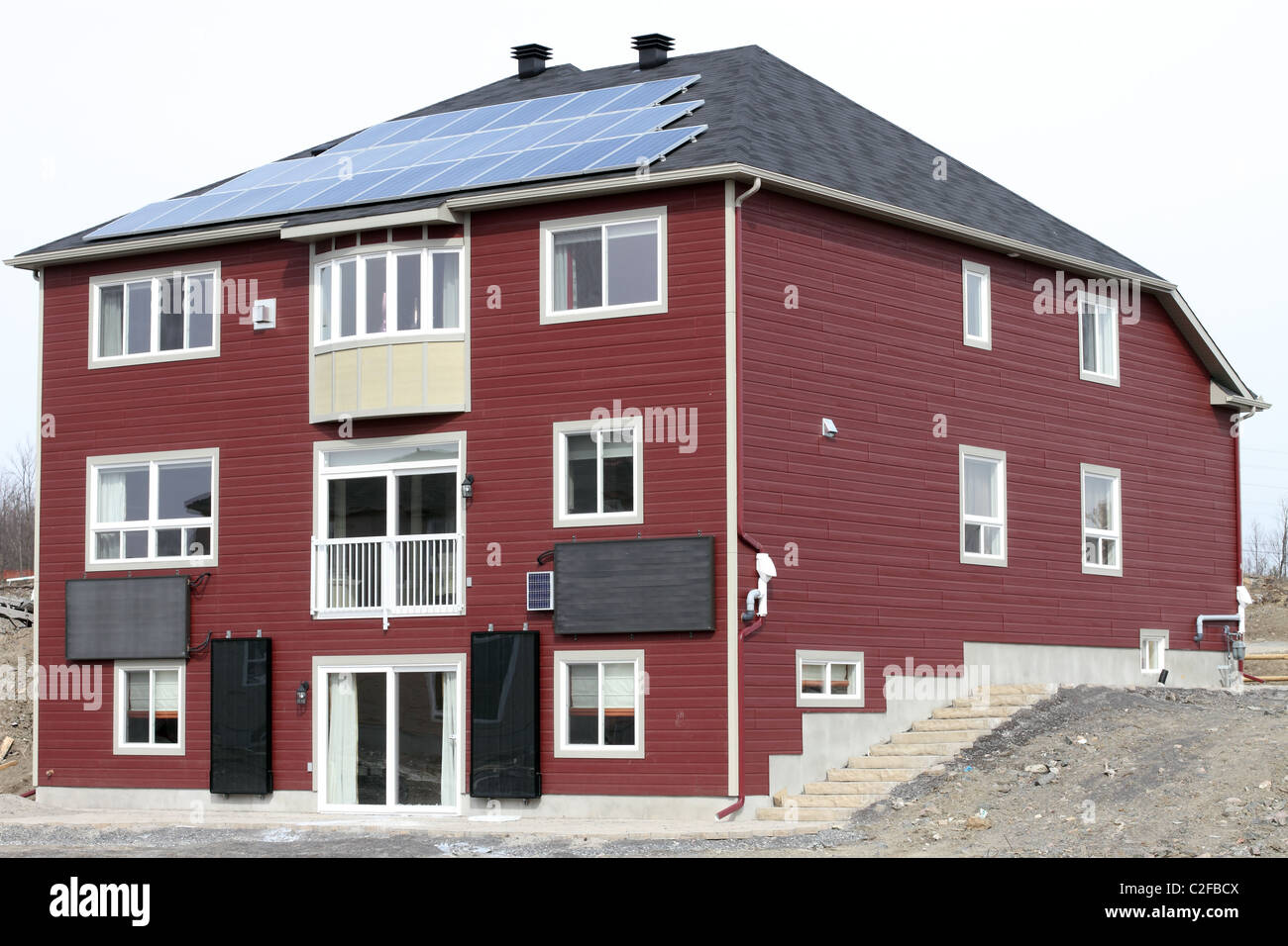 New Home Showcasing Green Energy With Solar Panels On The Roof And Solar Water Heaters On The Wall - Stock Image