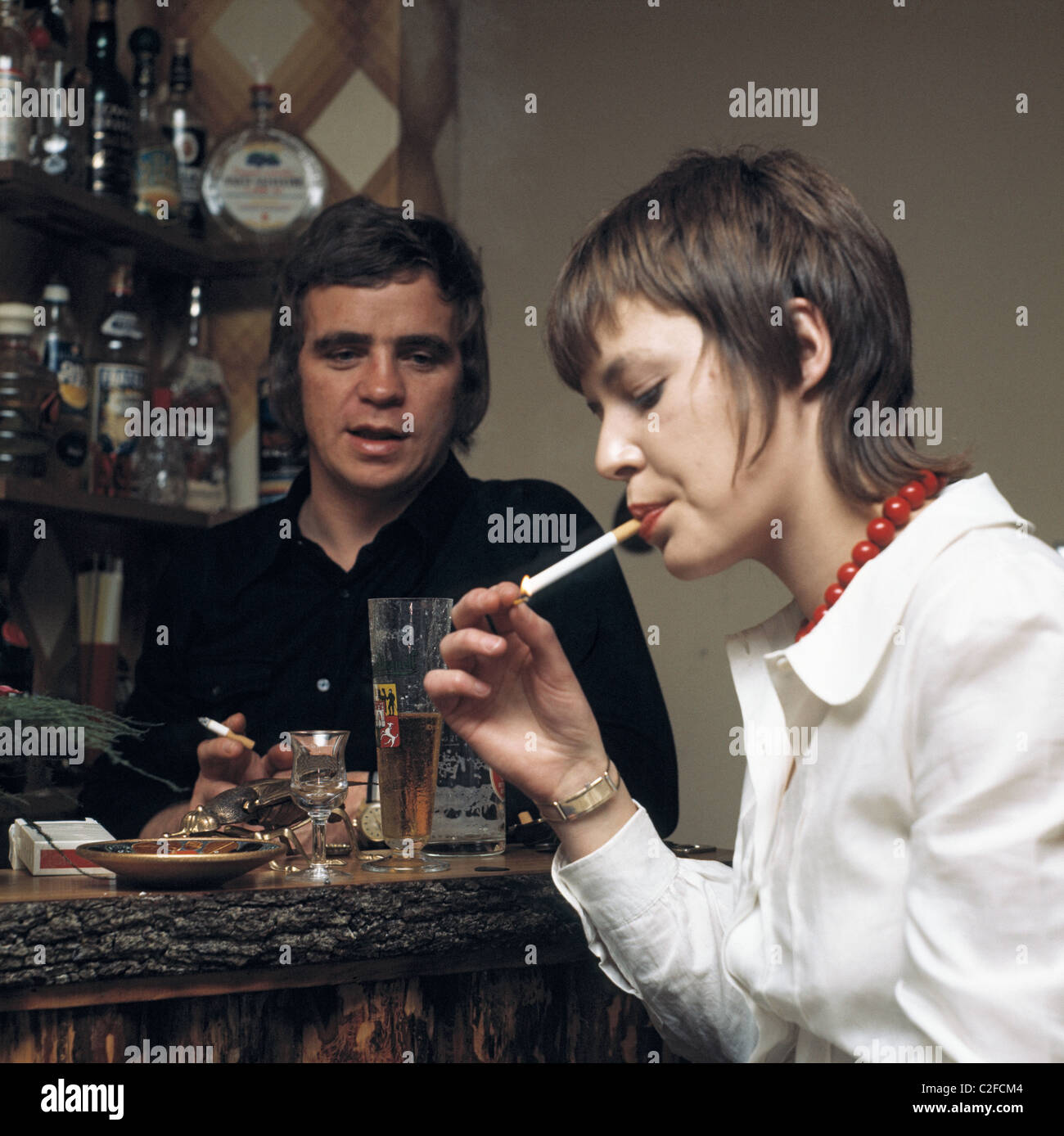 Seventies, people, freetime, semiluxury food, alcohol and tobacco, young woman and a man in a cellar bar, woman - Stock Image