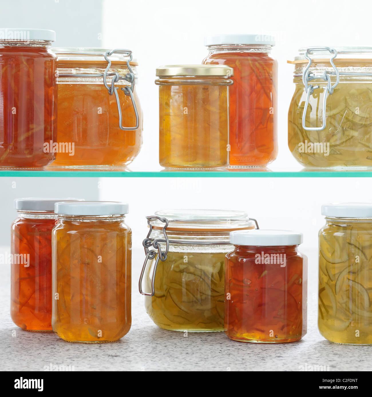 Home made marmalade jars on glass shelf - Stock Image
