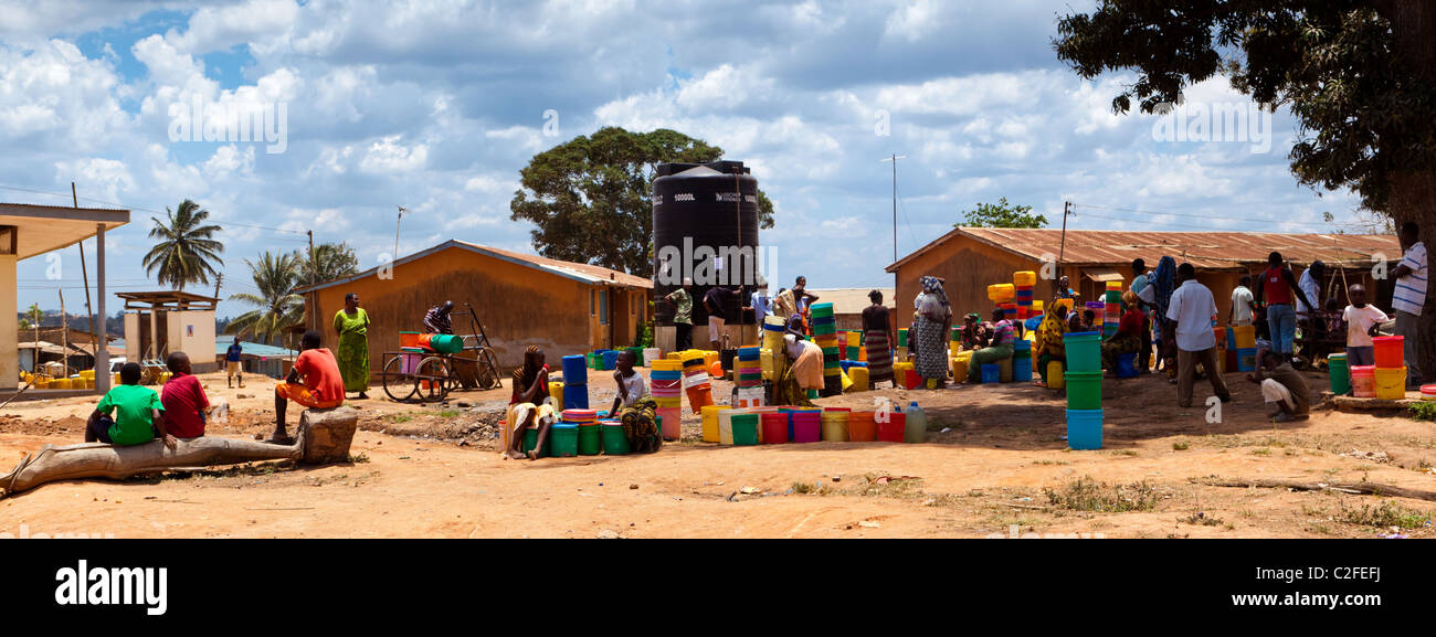 People gathering next to a water tower with brightly colored buckets. Kisarwe Village Dar es Salaam Tanzania - Stock Image