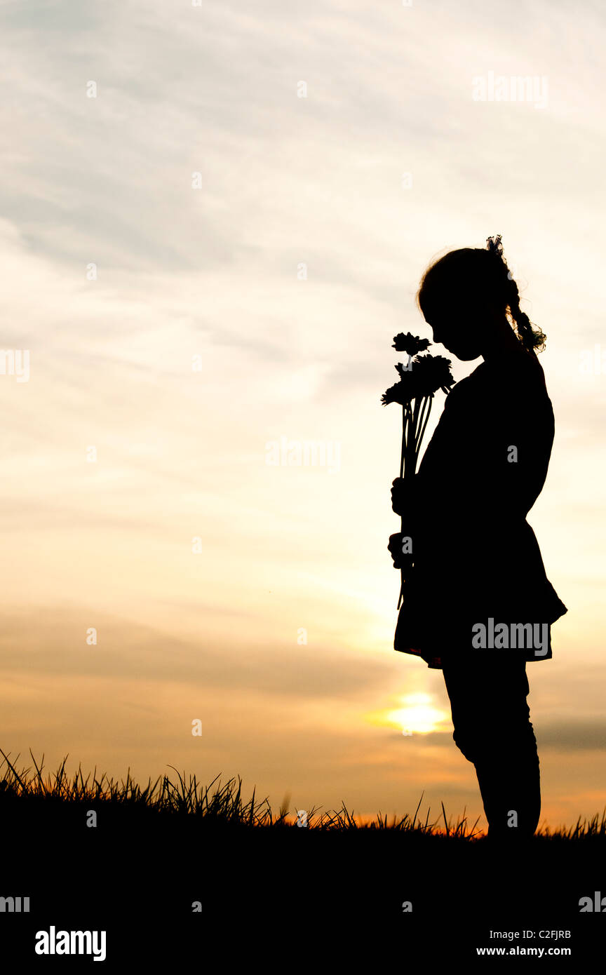 Solitary Young Girl standing holding flowers against a sunset. Silhouette - Stock Image