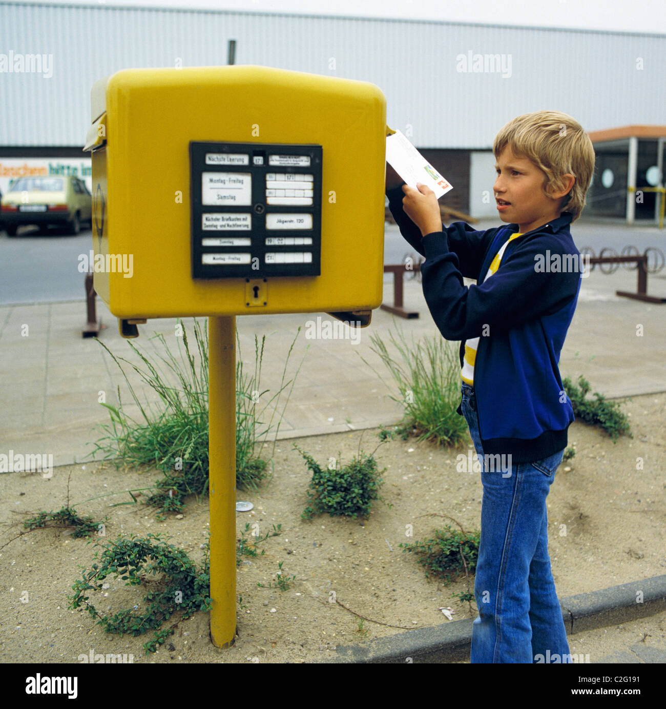 Eighties, people, communication, letter mail, child, little boy posts a letter into a mailbox, aged 7 to 10 years, - Stock Image