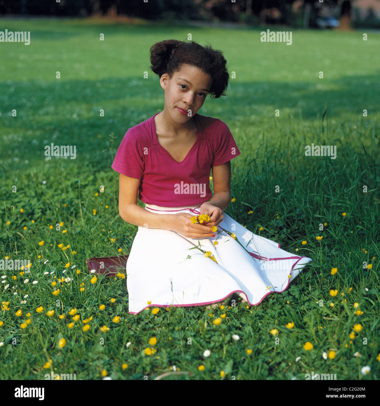 Eighties, people, child, young girl crouching on a flower meadow, portrait, aged 10 to 14 years, middle long hair, - Stock Image