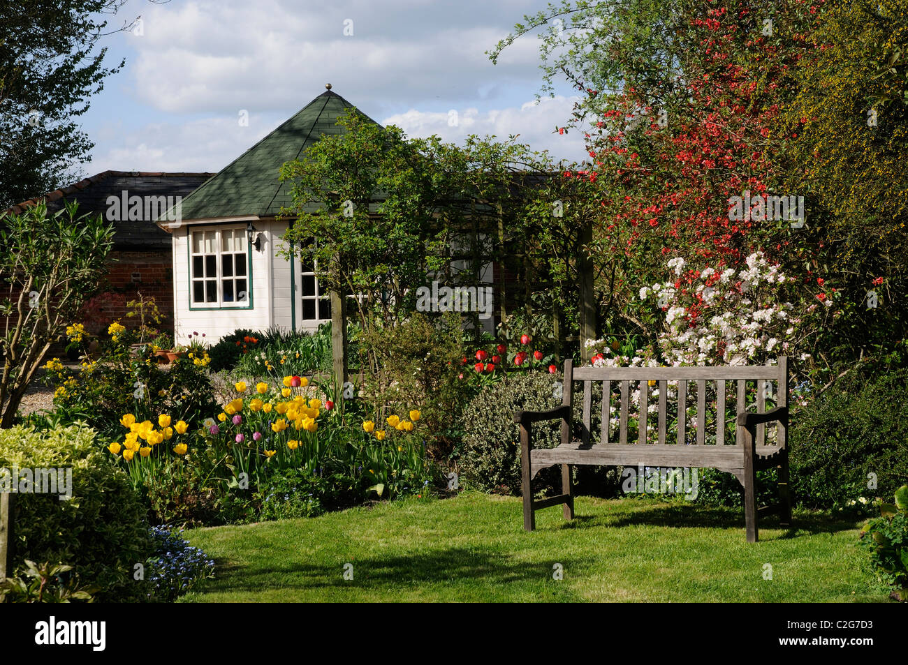 English Country Garden With Spring Flowering Plants A Summer House Office And Seat England