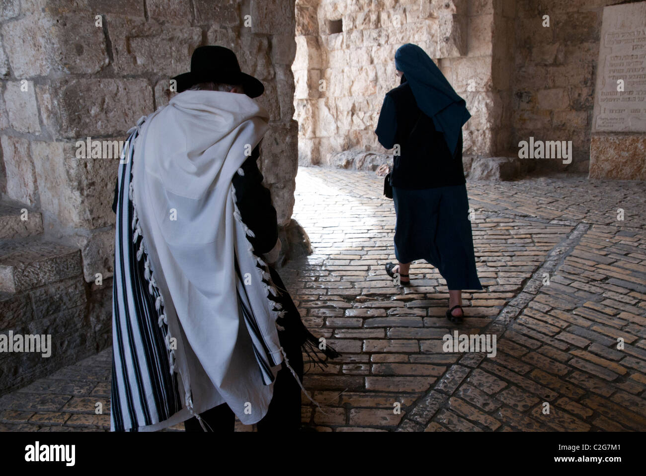 Orthodox Jew and nun walking through Zion gate. Jerusalem Old City. Israel - Stock Image