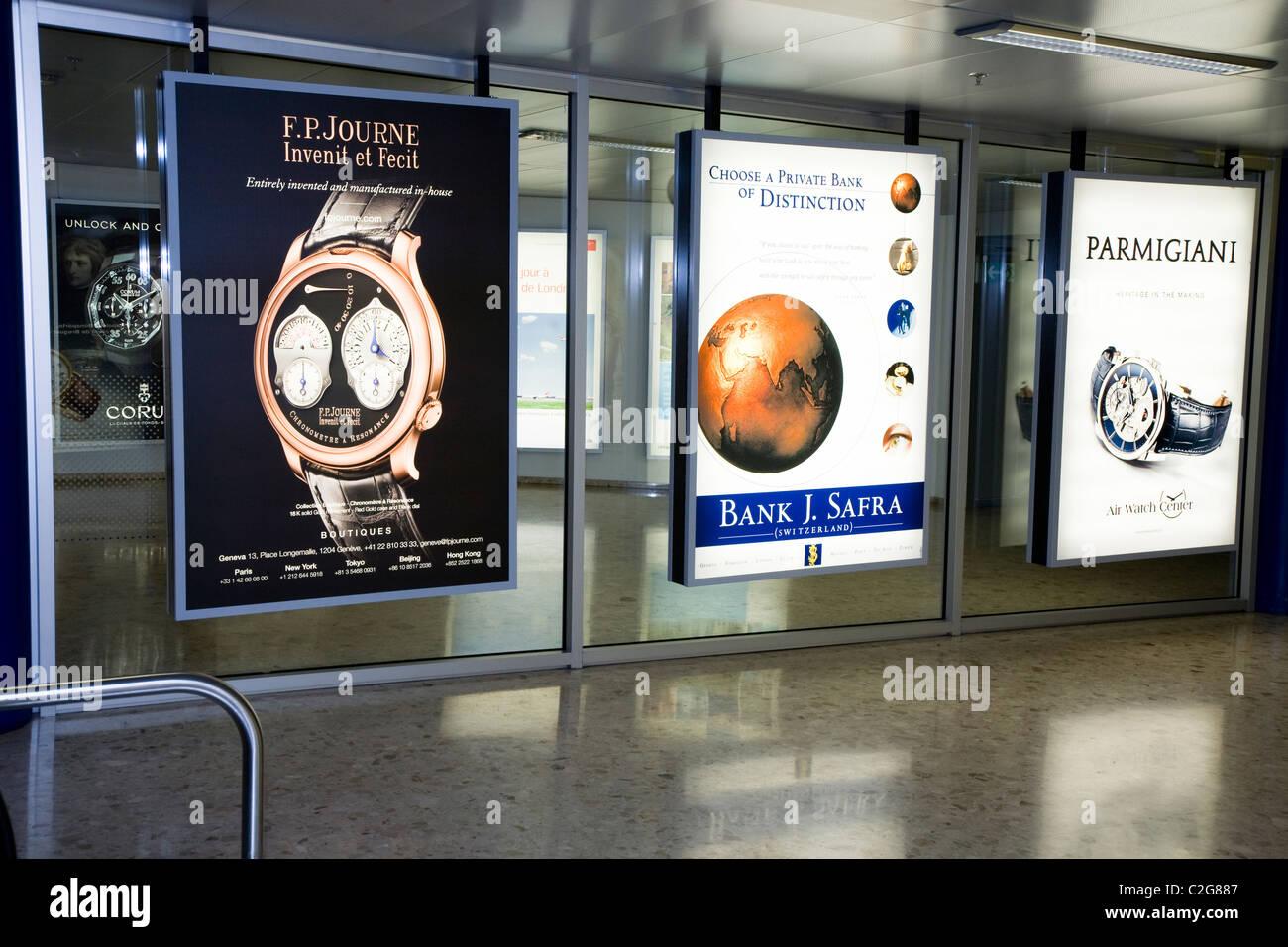Watch & bank adverts / advert sign / poster at International terminal departure hall, Geneva / Geneve Airport, - Stock Image
