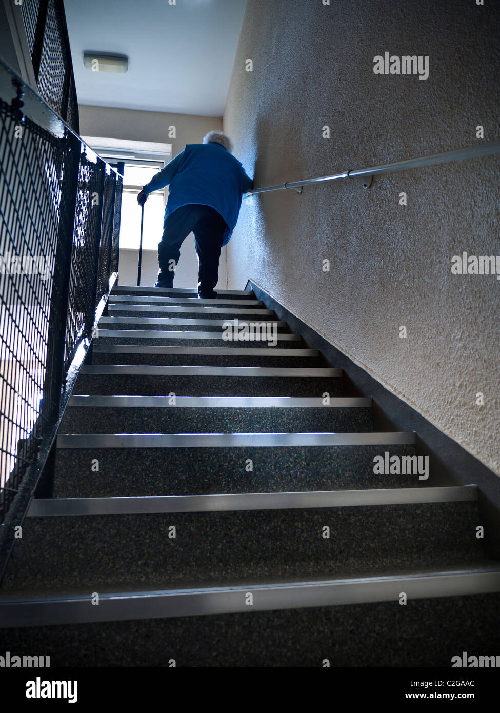 Independent elderly senior pensioner lady at 97 years climbing steep flight of stairs aided only by her walking - Stock Image