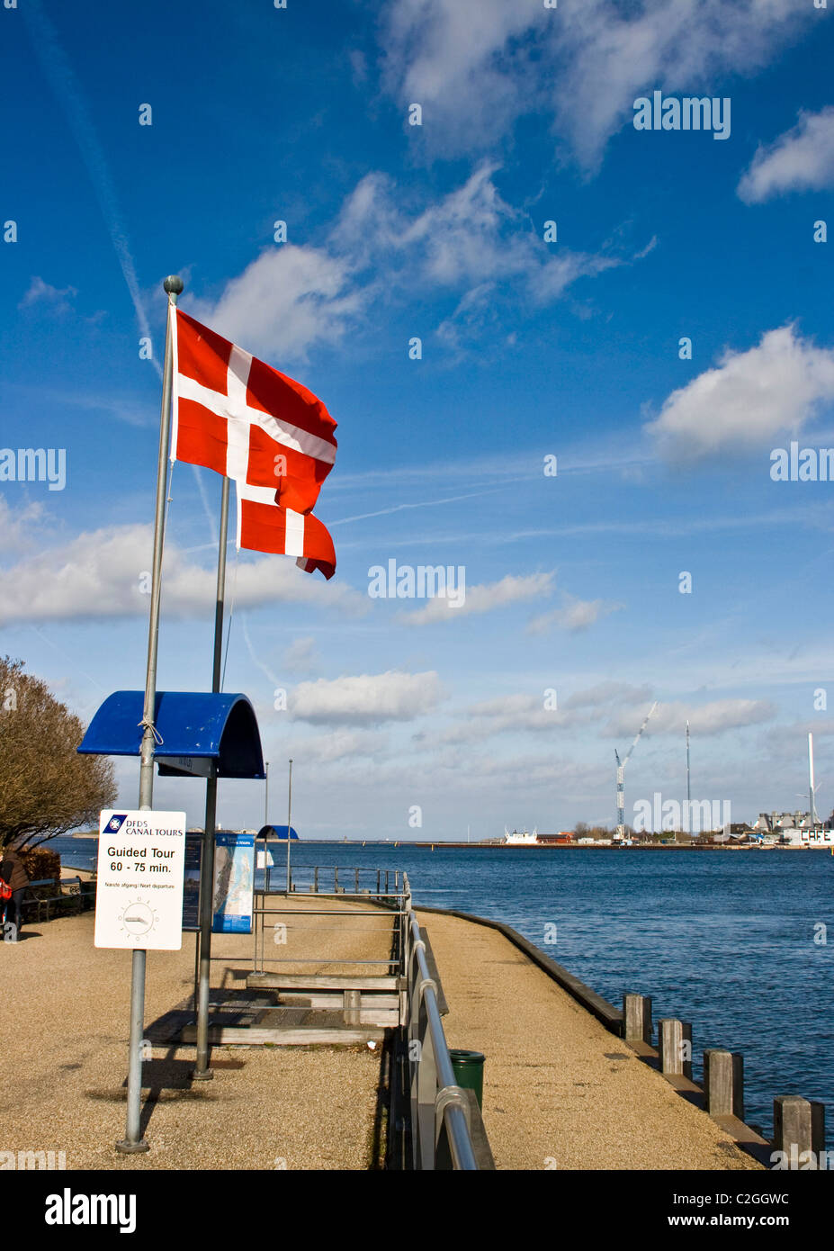 Two Danish (Dannebrog) flags flying waving against a blue sky Copenhagen Strait of Oresund Denmark Scandinavia Europe - Stock Image