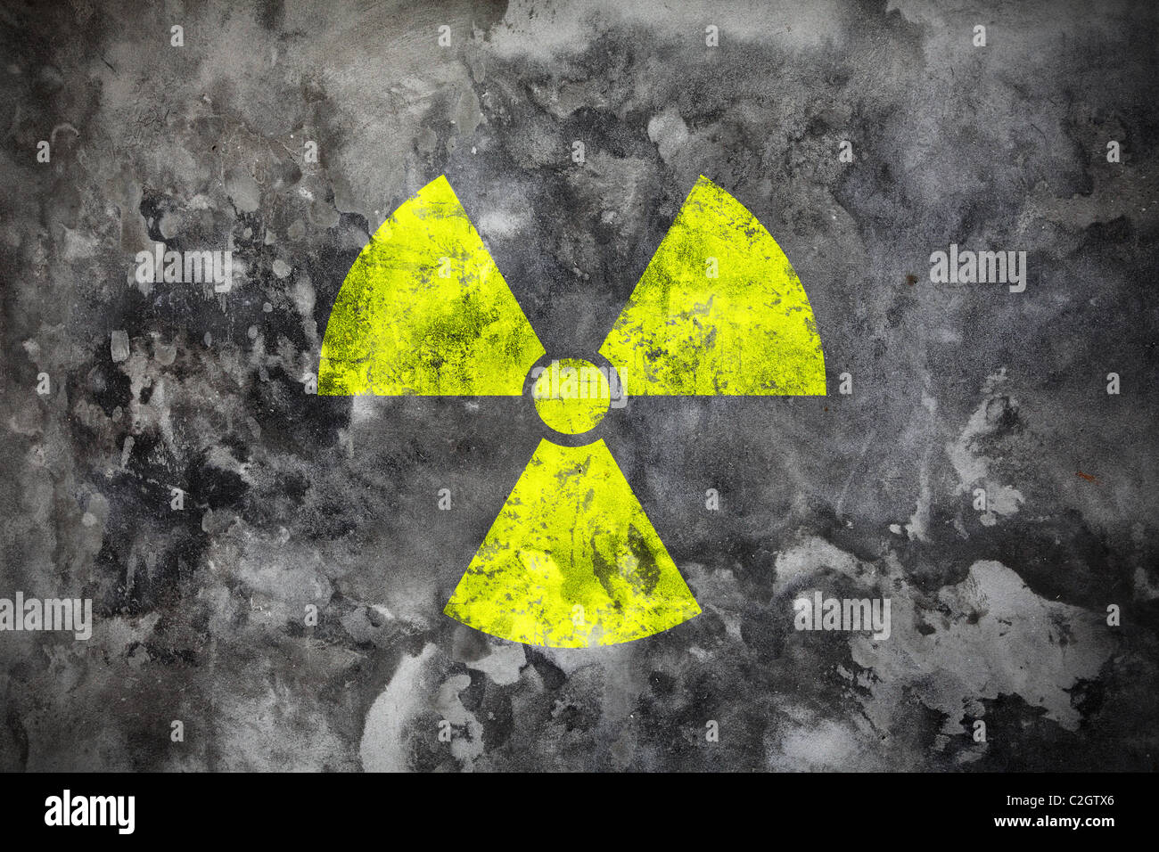 Concrete wall with yellow radiation sign - Stock Image