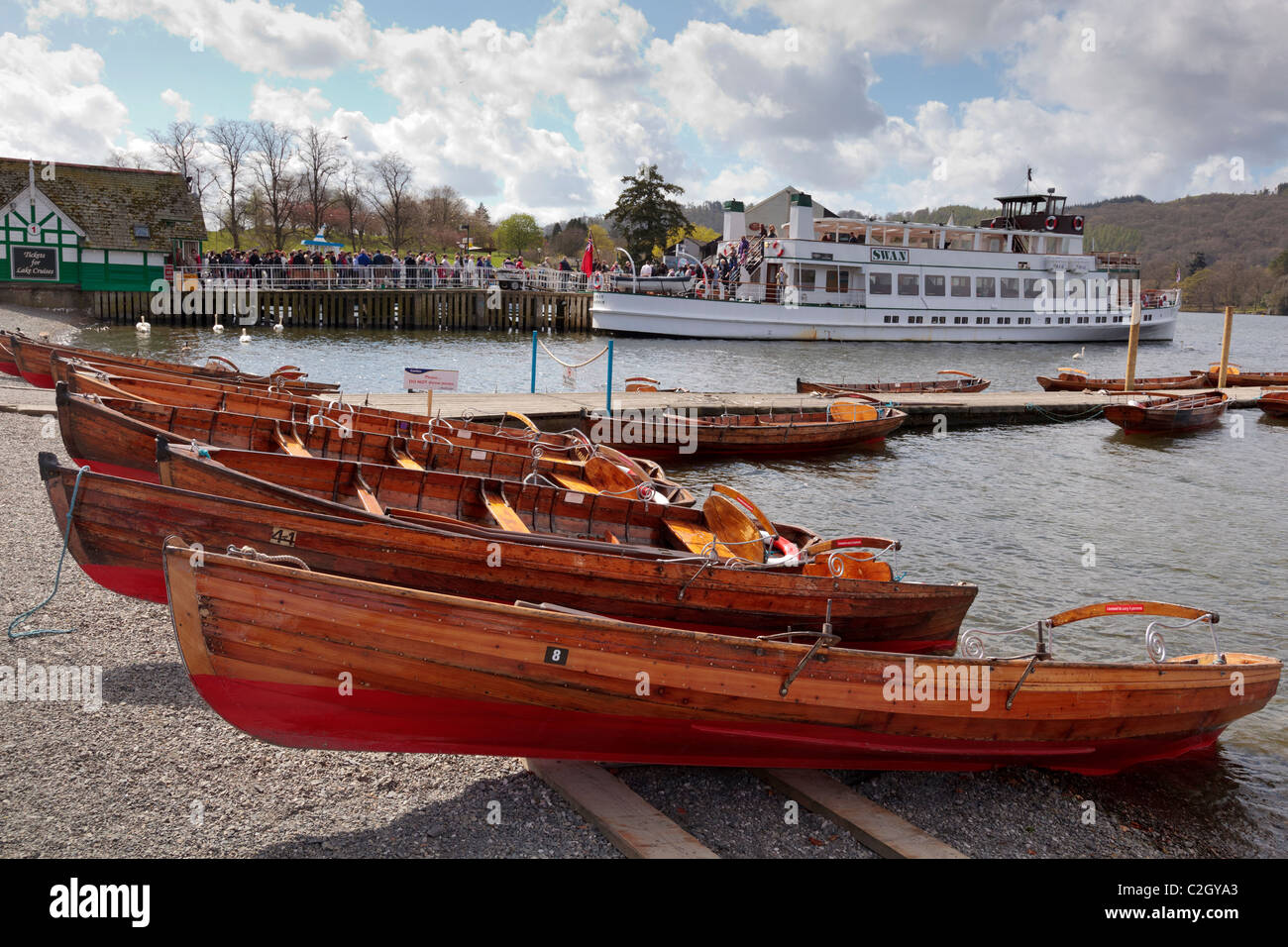 The pier at Bowness on Windermere in the lake district  with the steamer Swan and rowing boats. - Stock Image