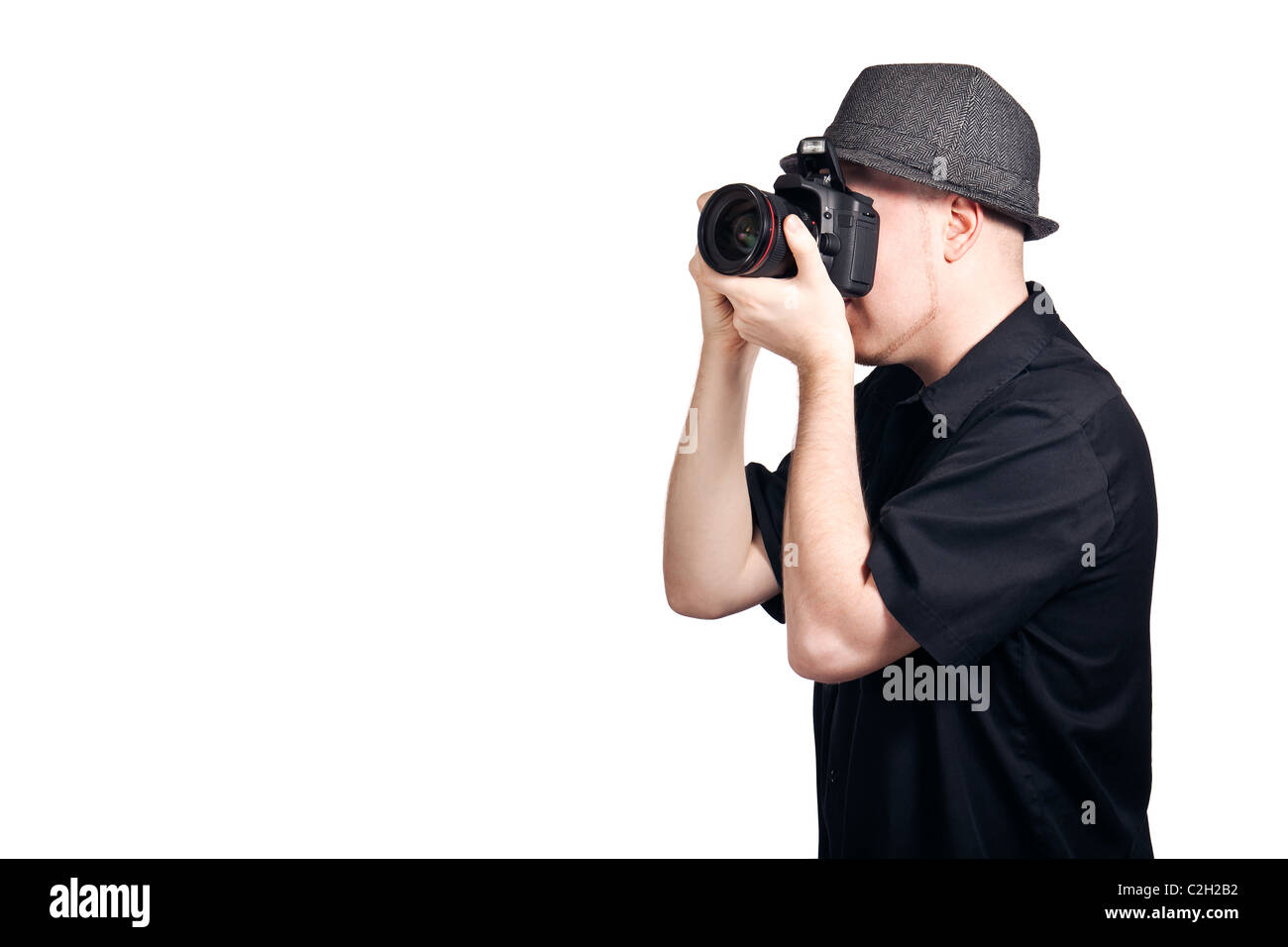 A young man looking through the viewfinder of an SLR camera and focusing to take a photo. - Stock Image