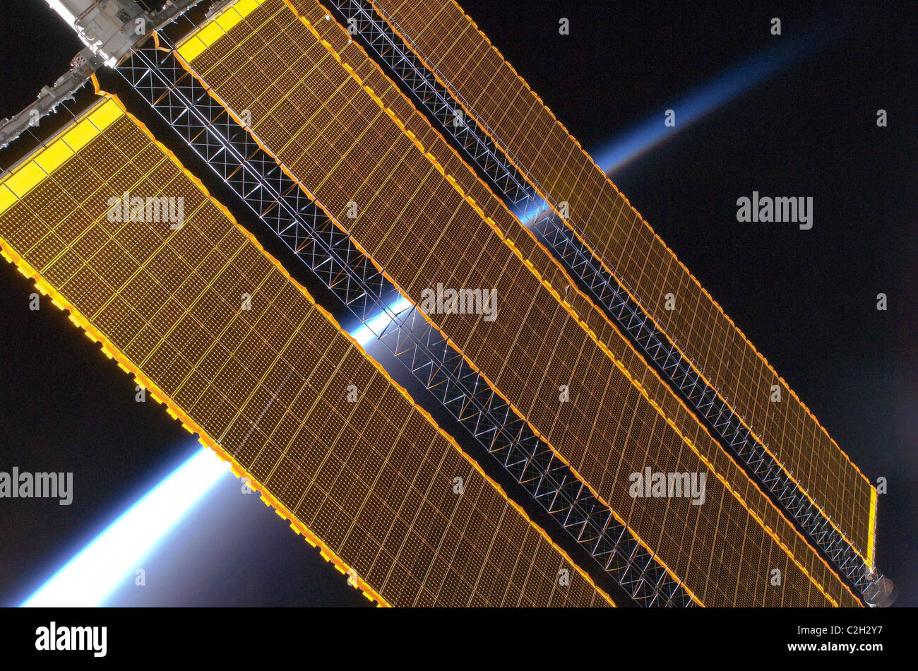 Earth's horizon and the International Space Station's solar array panels. Stock Photo