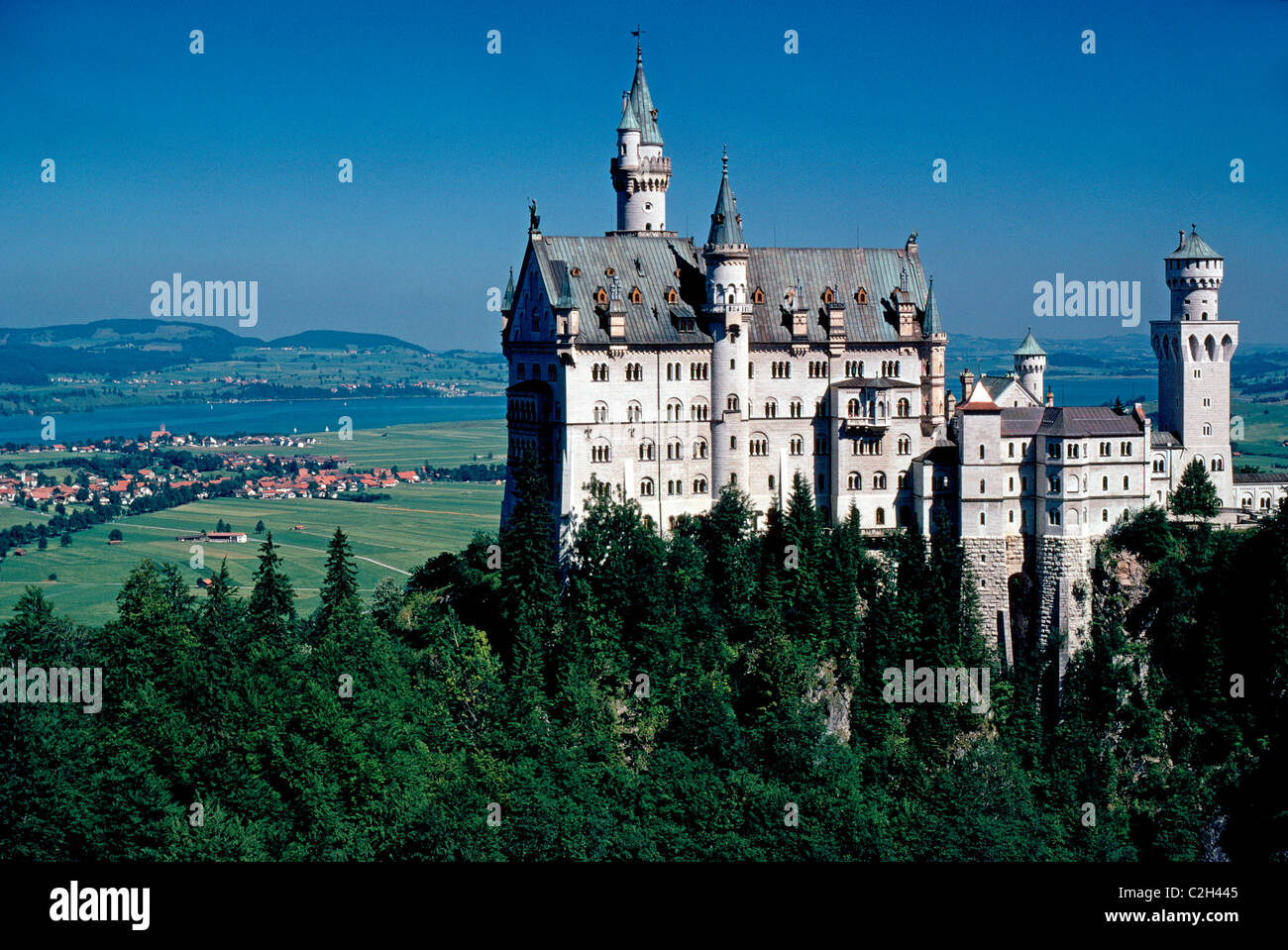 Neuschwanstein Castle is the famous 19th-century royal palace of Mad King Ludwig II on a hill above the village - Stock Image