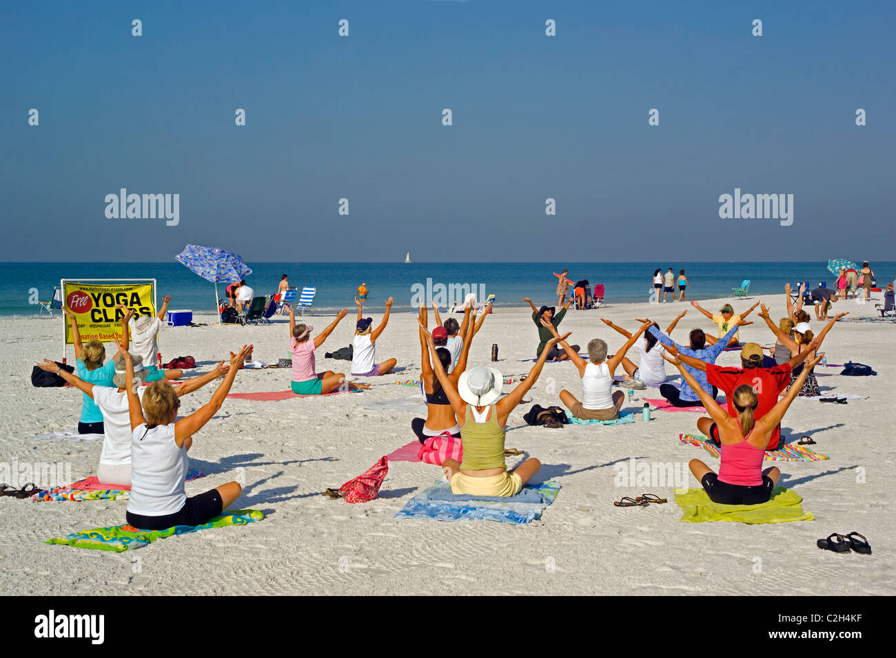 Yoga classes are held on the white sand beach of Siesta Key, a resort barrier island on the Gulf of Mexico at Sarasota, - Stock Image