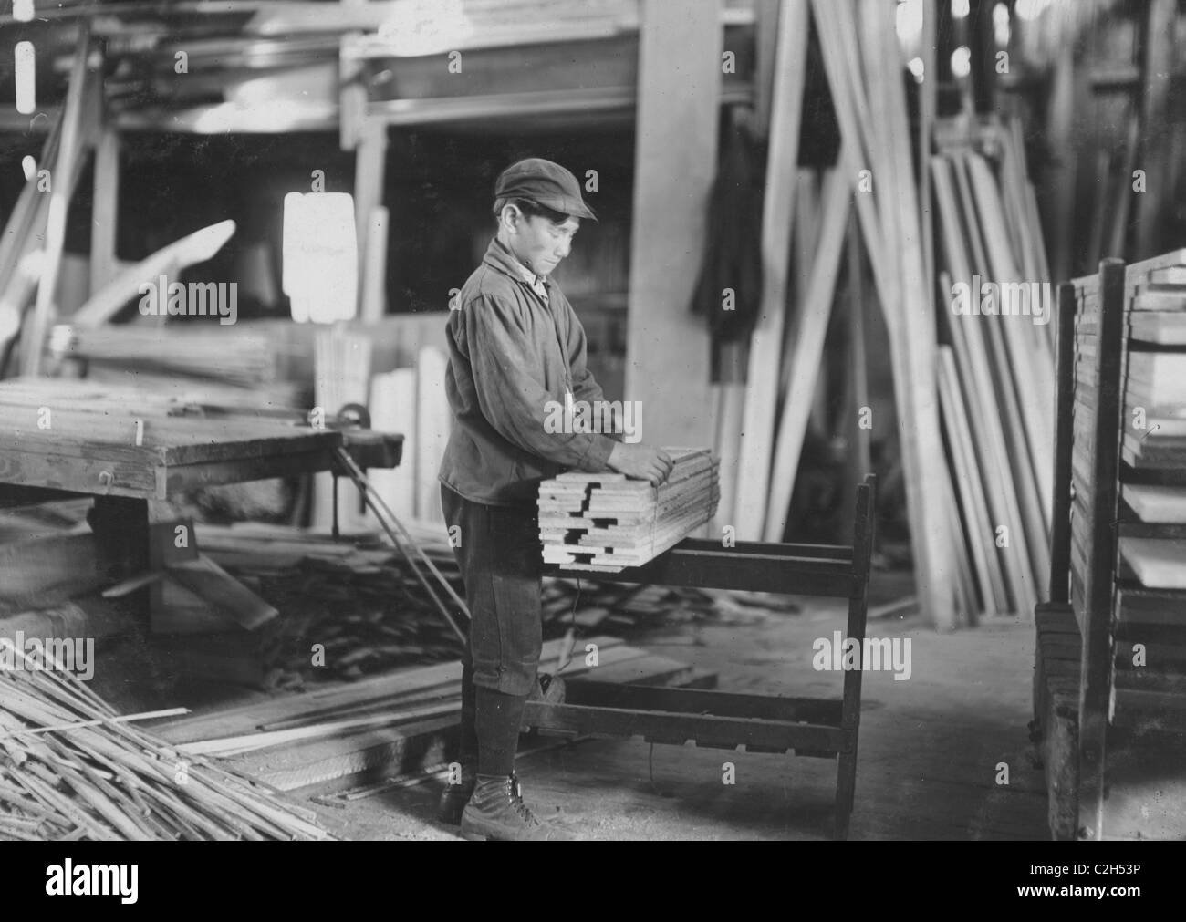 Boy probably about 13 years old, tying strips which he has taken away from the planer - Stock Image