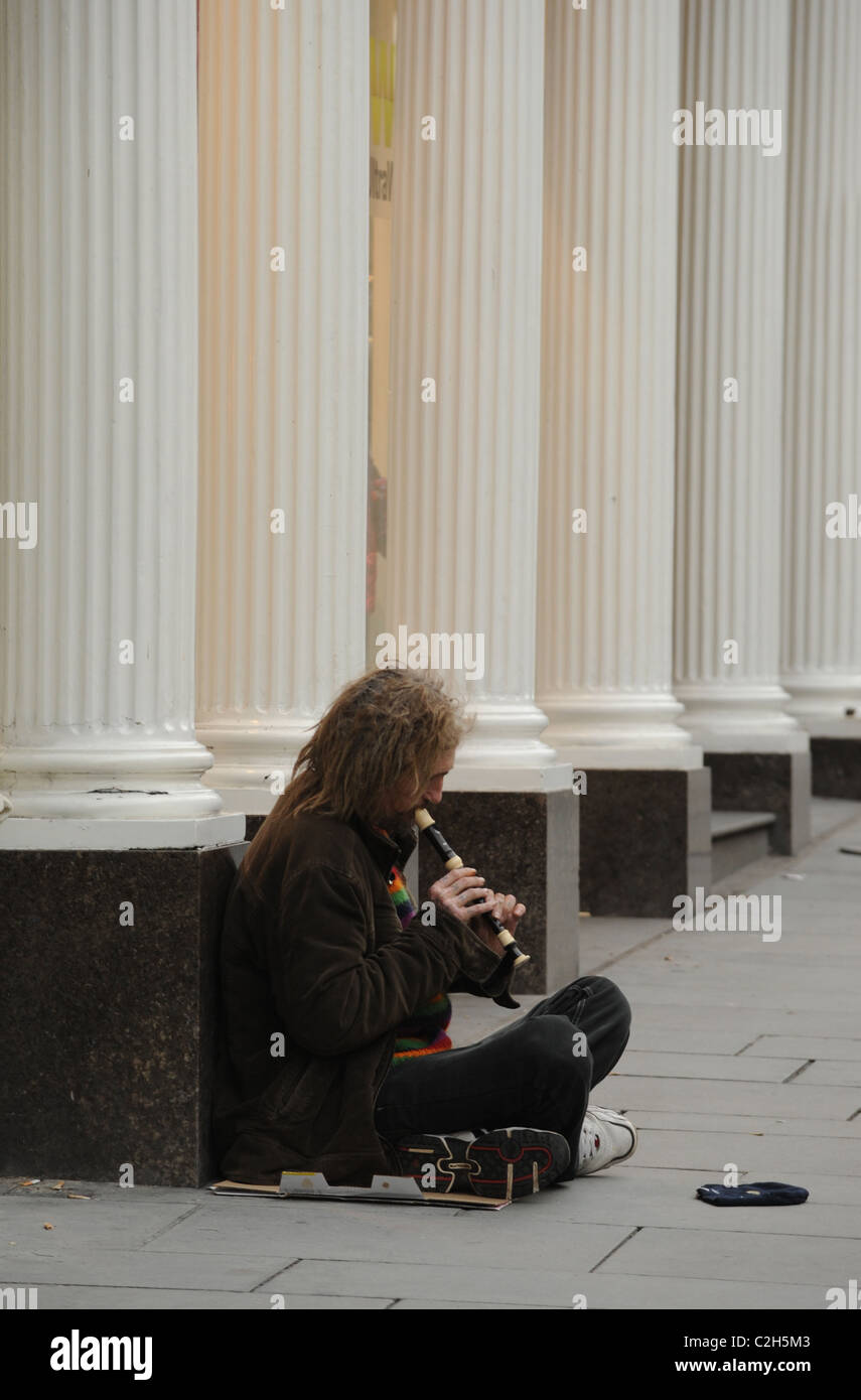 A beggar plays for money, the odd coin from a passing stranger. - Stock Image