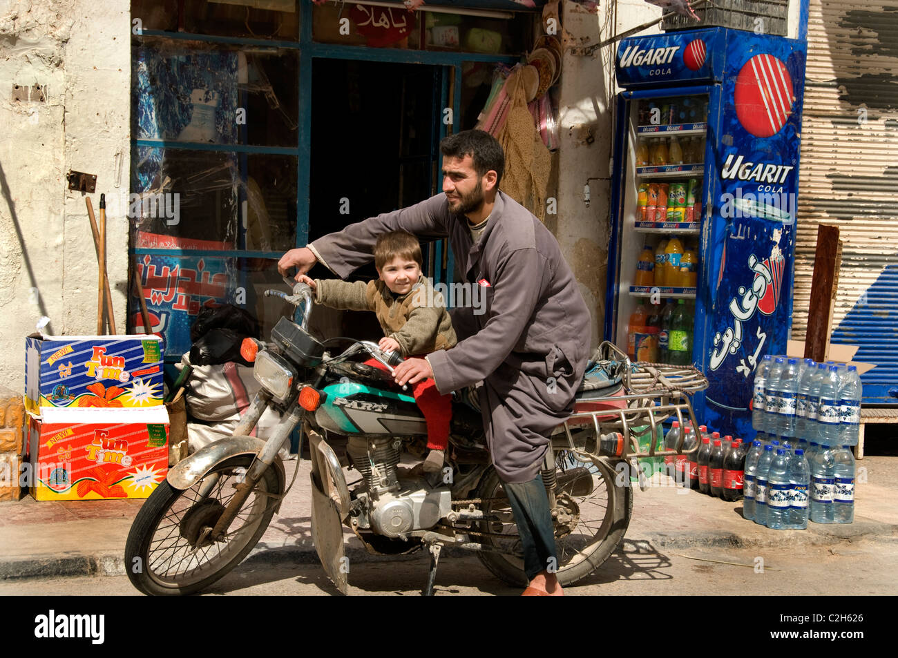 Palmyra new town city Syria Syrian motorcycle father young boy motorbike - Stock Image