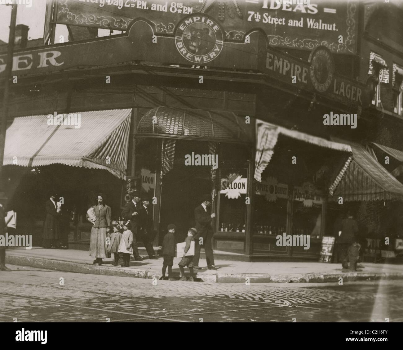 Newsies selling near saloon. - Stock Image