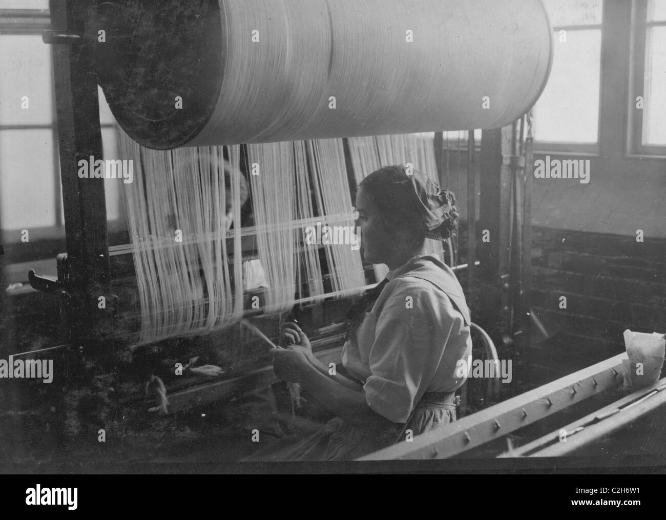 Girl at the drawing-in-frame of the weave-room, Lorraine Mills, Pawtucket, R.I. - Stock Image