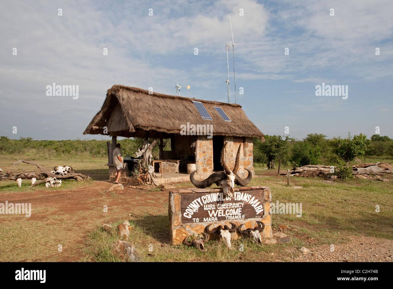 Solar PV panels & wind turbine on thatched roof game reserve entrance Masai Mara Kenya - Stock Image