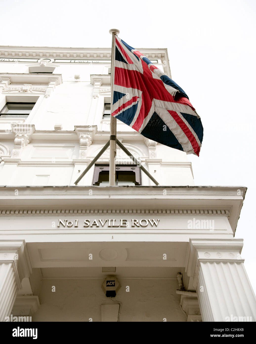Union Jack or national flag flies from flagpole at Number One Saville Row, the home of fine tailoring in London's - Stock Image
