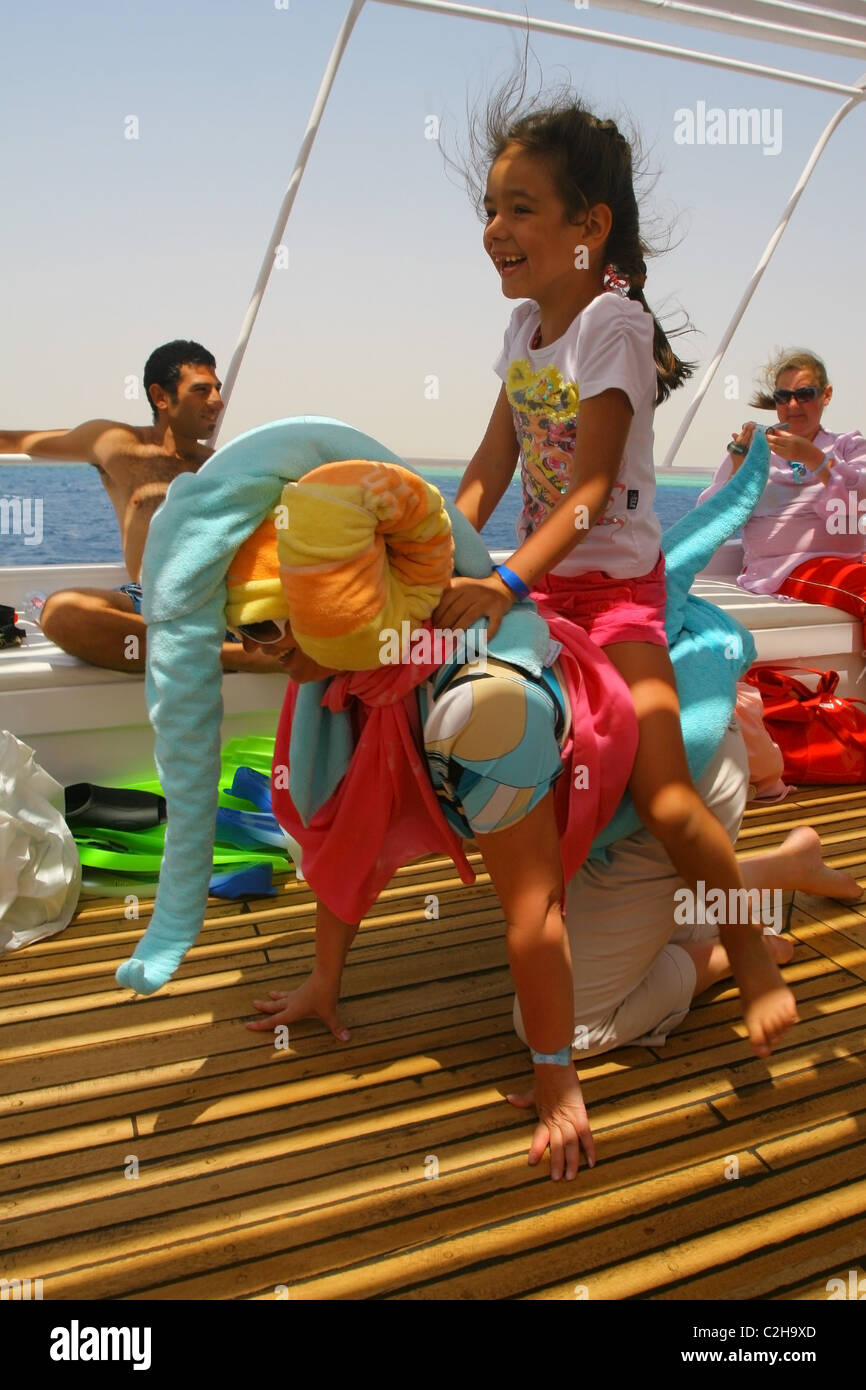 Girl happy with riding her mother, who give an imitation of an elephant with towels. Red Sea, Egypt - Stock Image