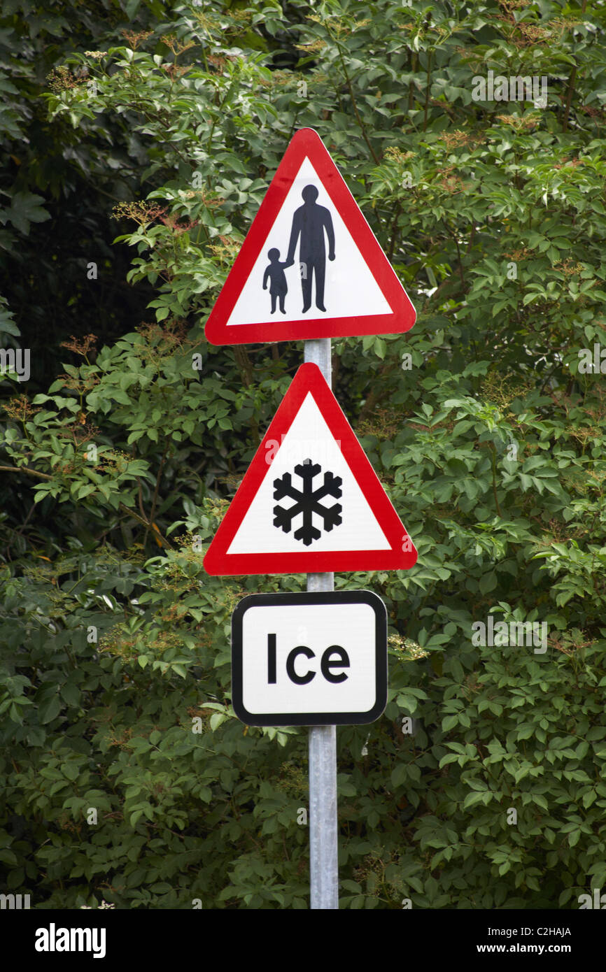 Road signs advising of Ice and caution pedestrians ahead - triangular road sign triangle Stock Photo