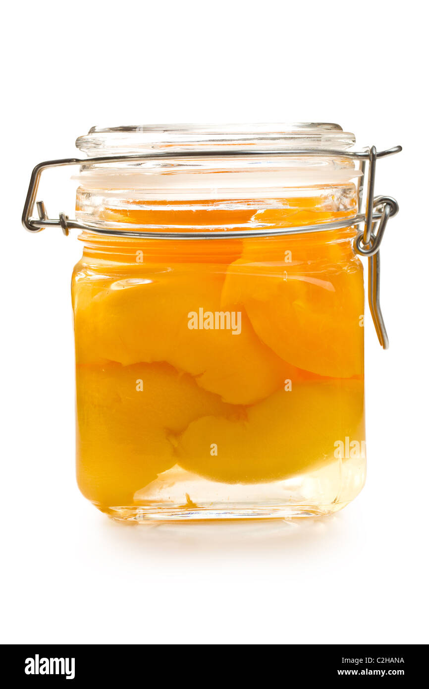 canned peach in glass jar on white background - Stock Image