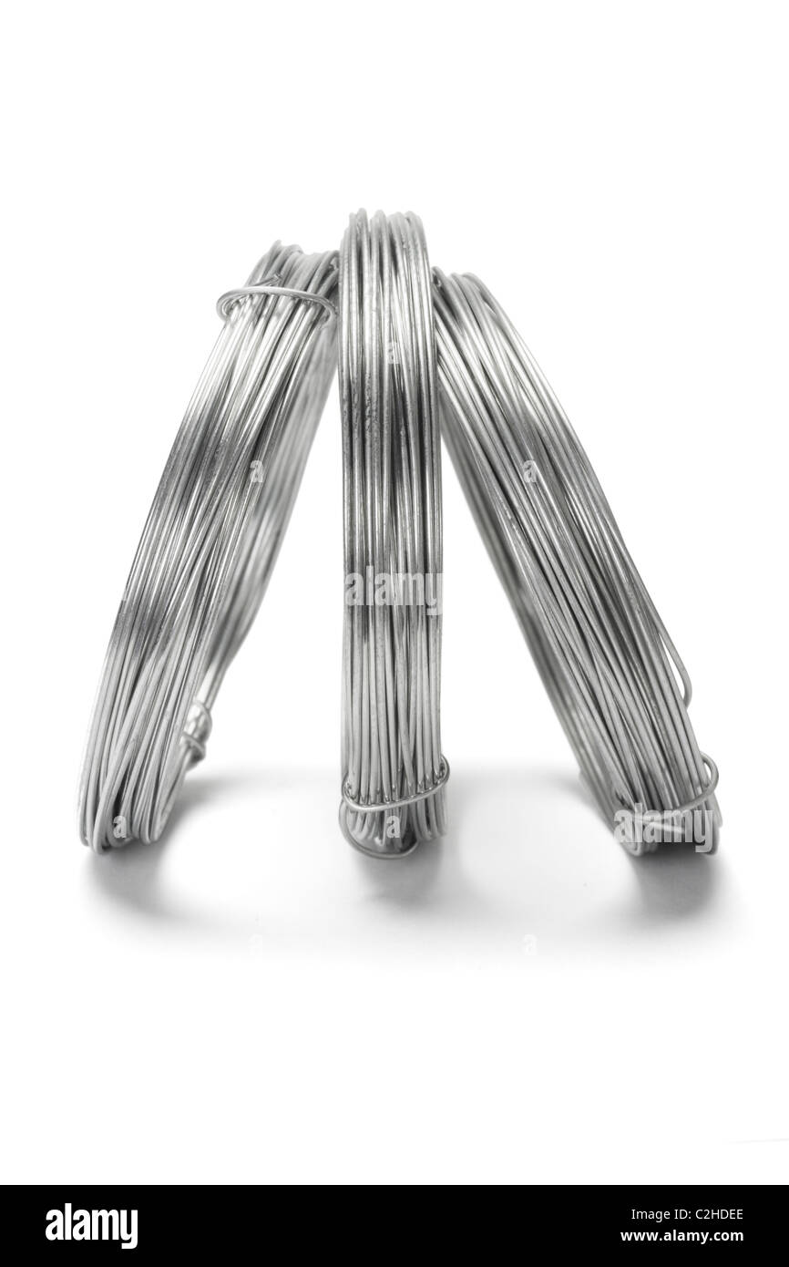 Coils of galvanized wires standing on white background - Stock Image