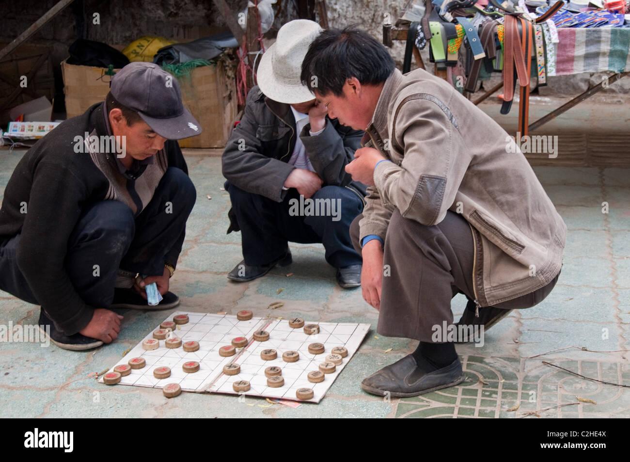 Chinese men playing Xiangqi, or Chinese Chess at Shigatse, TIbet - Stock Image