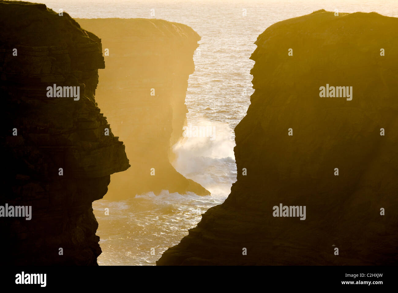 Sunset illuminates a chasm in the atlantic cliffs near Loop Head, County Clare, Ireland. Stock Photo