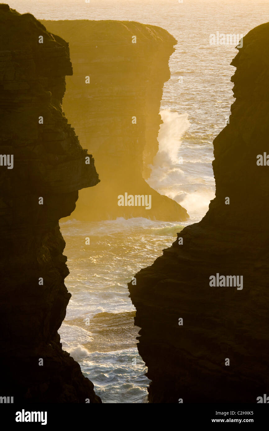 Sunset illuminates a chasm in the atlantic cliffs near Loop Head, County Clare, Ireland. - Stock Image