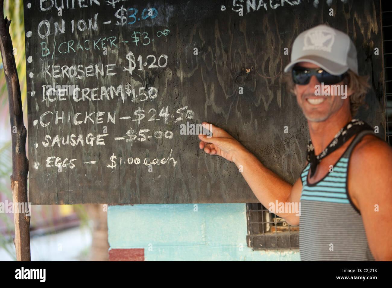 Brad Osborn on tour of island shop finds humor in price on menu board. - Stock Image