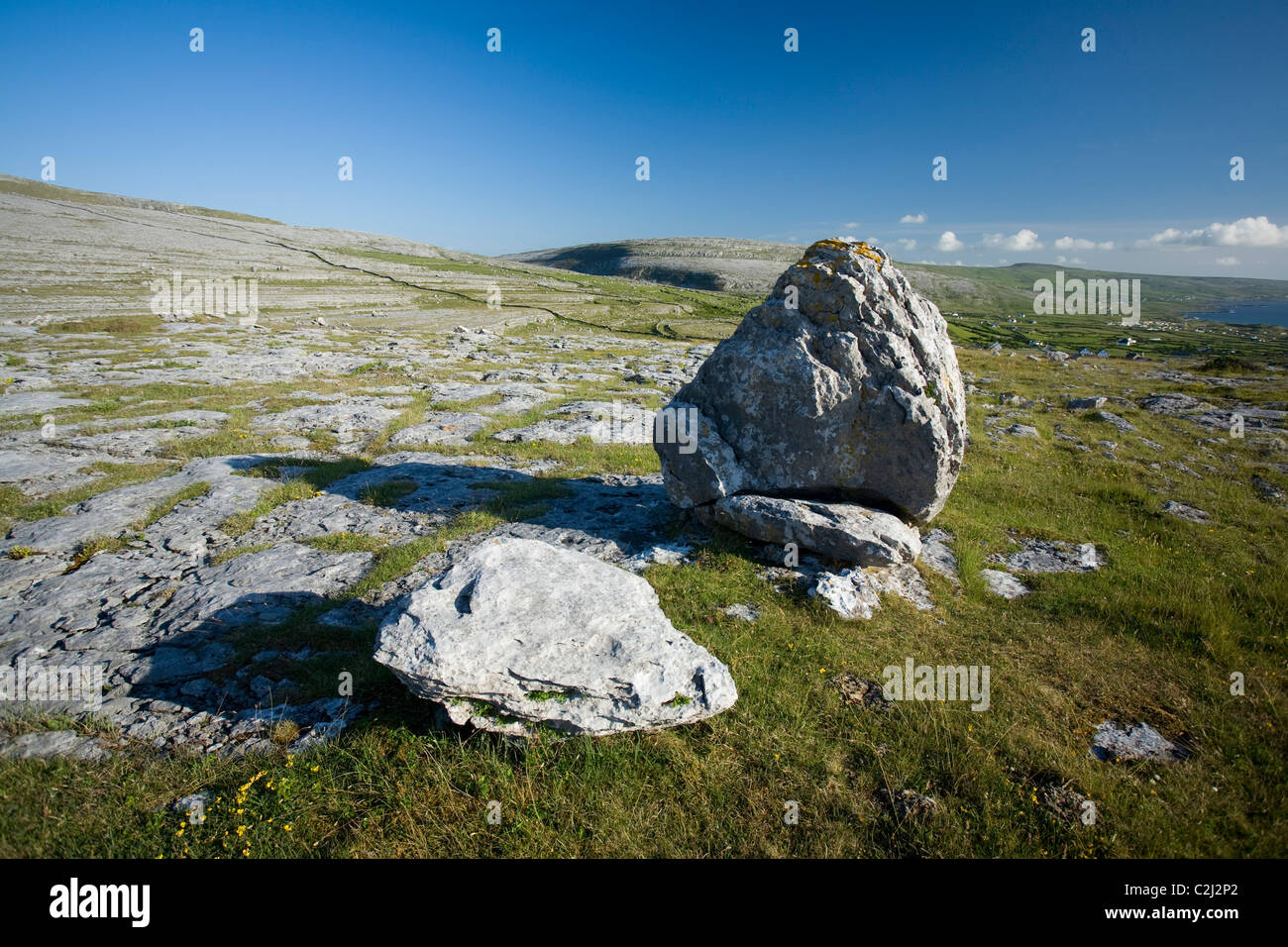 Limestone pavement and glacial erratic boulders in The Burren, County Clare, Ireland. - Stock Image