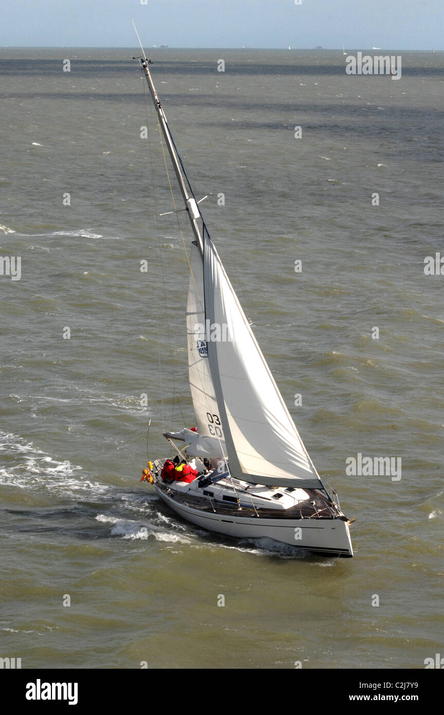 A yacht with sails reefed in sails close to the prevailing wind on a sunny spring day. Sail numbers modified. - Stock Image