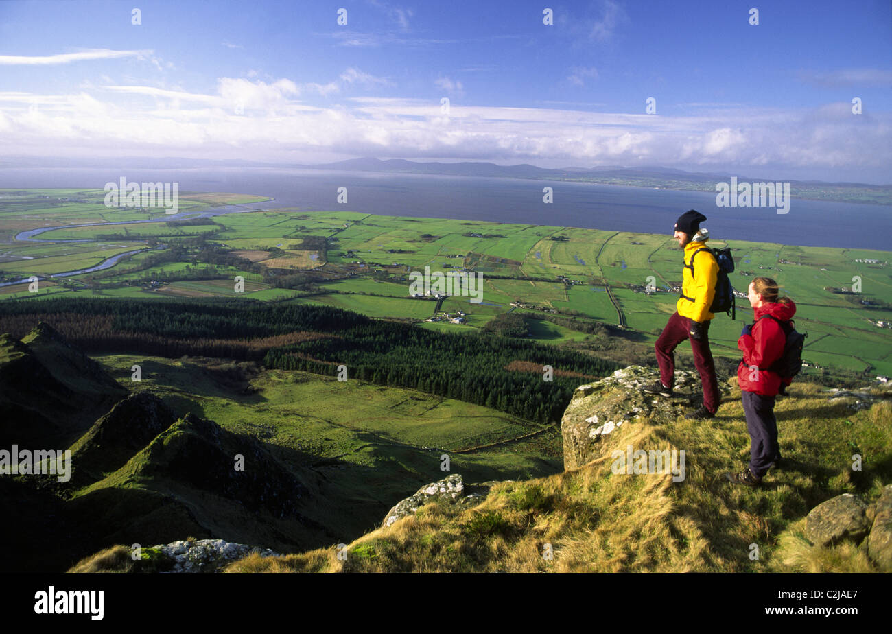 Walkers looking over Magilligan Point from the summit of Binevenagh, County Derry, Northern Ireland. - Stock Image