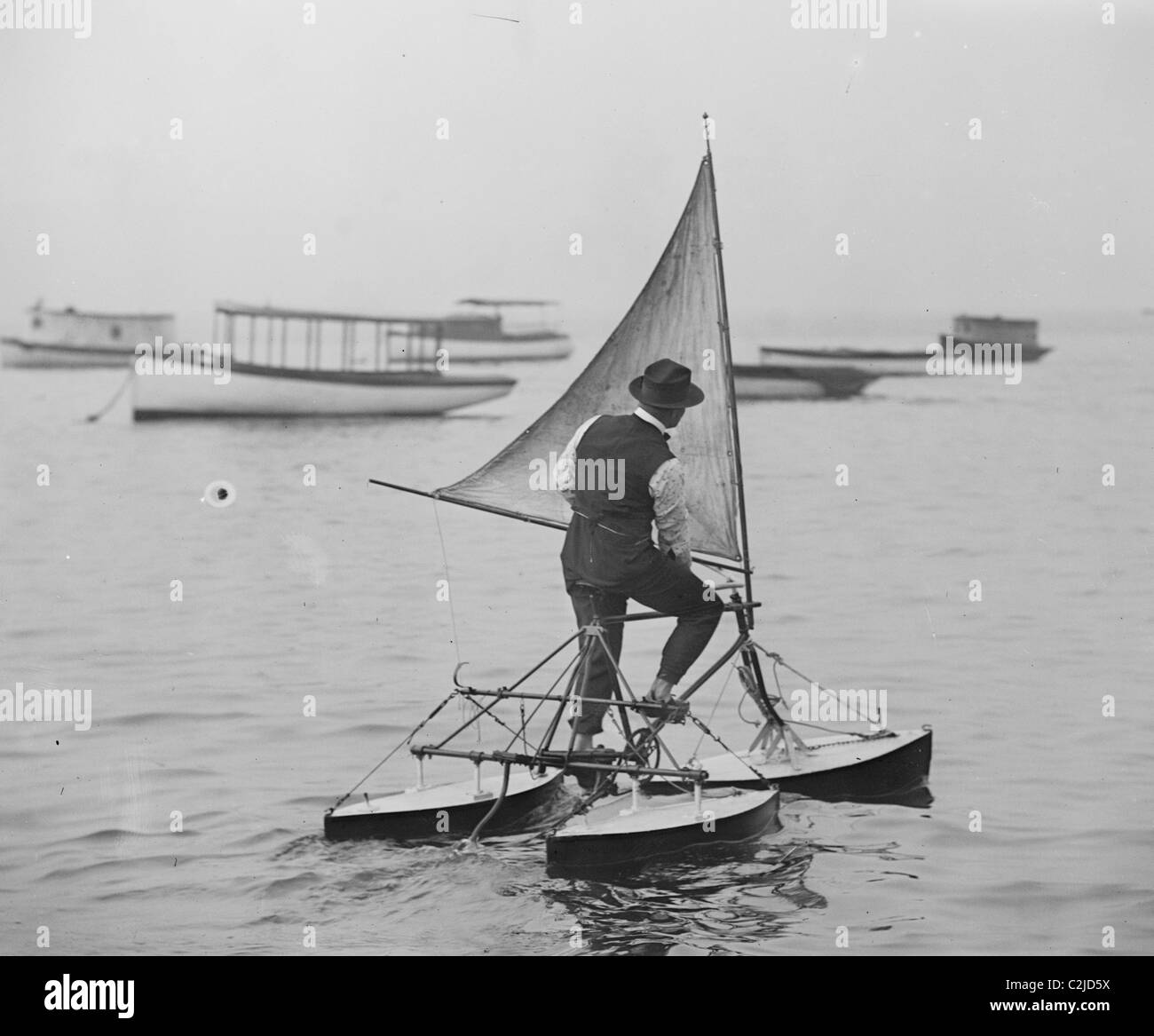 Man stands on Sail Driven water Tricycle - Stock Image