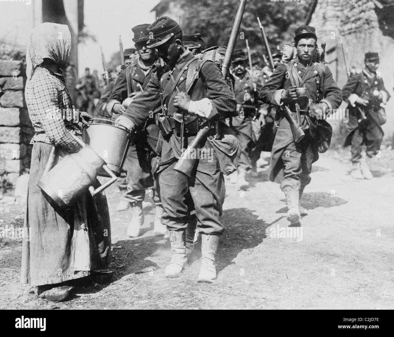Peasant Woman provides water to passing French Troops - Stock Image