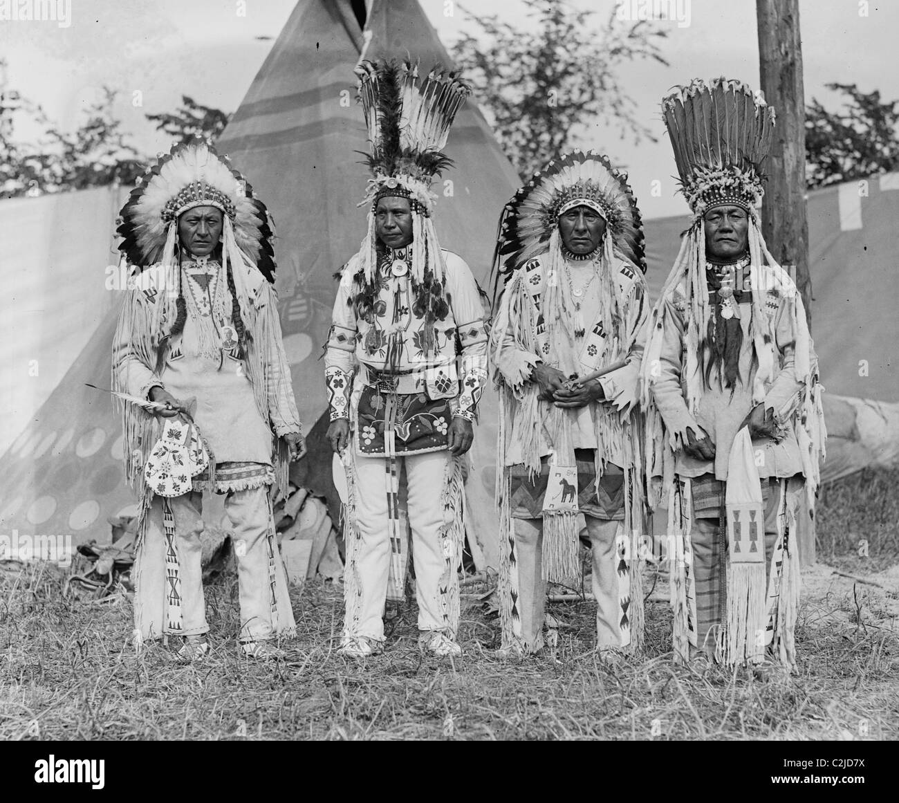 Four Native American Chiefs in Traditional Clothing and Feathered Bonnet - Stock Image