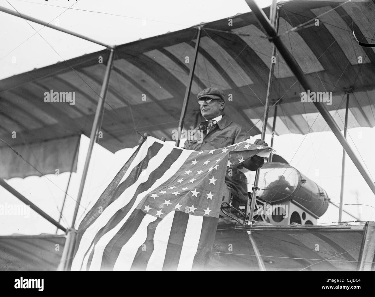 Aviator C.B. Harmon Unfurls Stars and Stripes from his pilot seat on his Biplane. - Stock Image