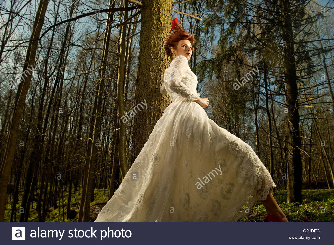 Young Woman in a Vintage Wedding Dress Young Woman in white vintage wedding dress is standing near the tree in the Stock Photo